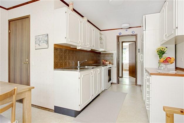 Kök med vit inredning och ingång till tvättstugan.