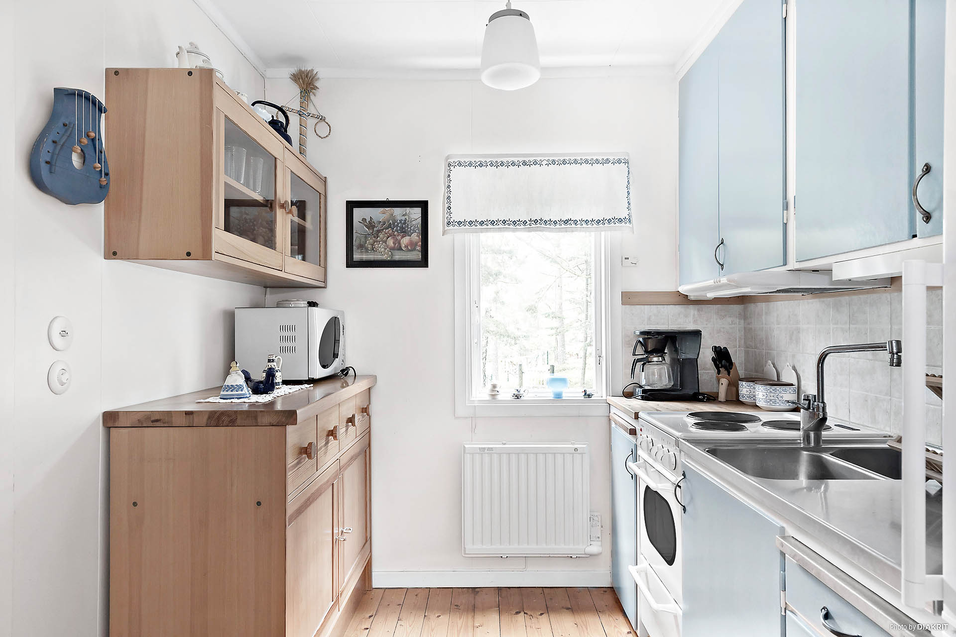 Köket har en välskött standard och bra med förvaring. Det är utrustat med spis och kyl. Trivsamt med ljusinsläpp från fönster.
