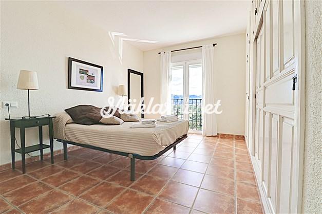 Rymligt sovrum med garderobsvägg och fransk balkong