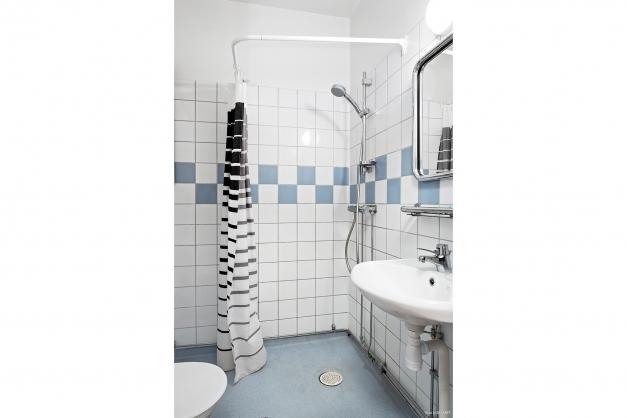 Halvkaklat badrum med dusch