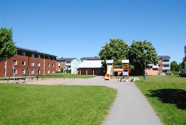 Angränsande innergården med  bl. a. lekplats och utegrill (arkivbild, sommar)