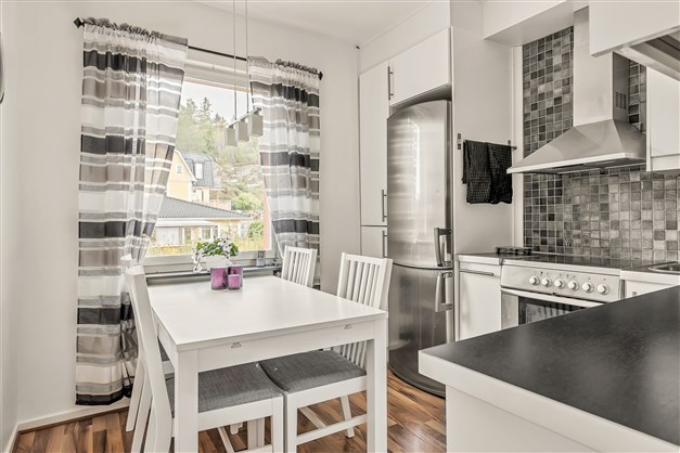 Stilrent kök med matplats för 4-5 personer intill fönster med utsikt över grönska