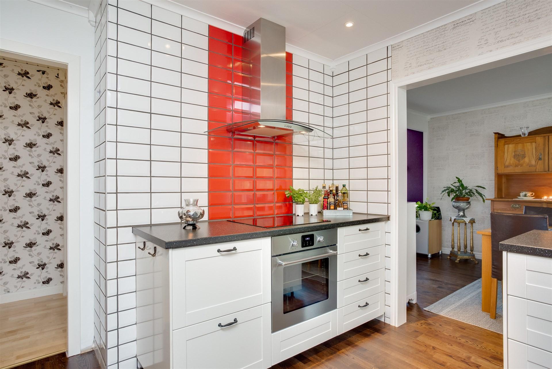Färgdetaljer bakom köksfläkt och vid arbetsbänk.
