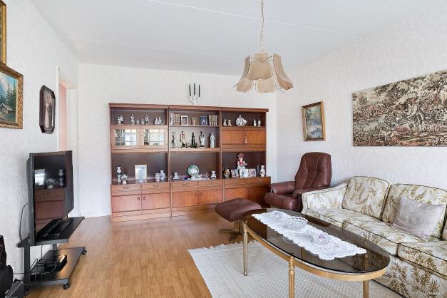 Luftigt vardagsrum med ingång till kök och hall