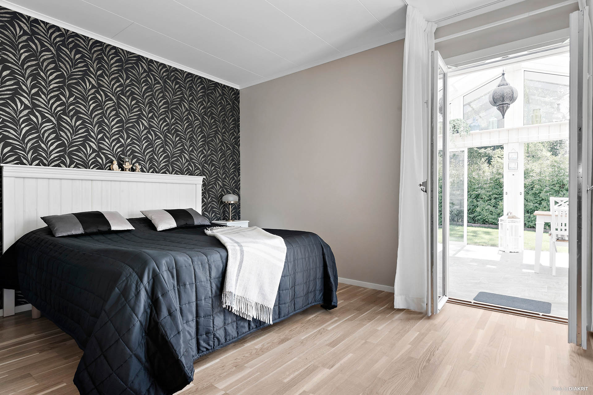Generöst sovrum med fransk dörr mot vinterträdgården