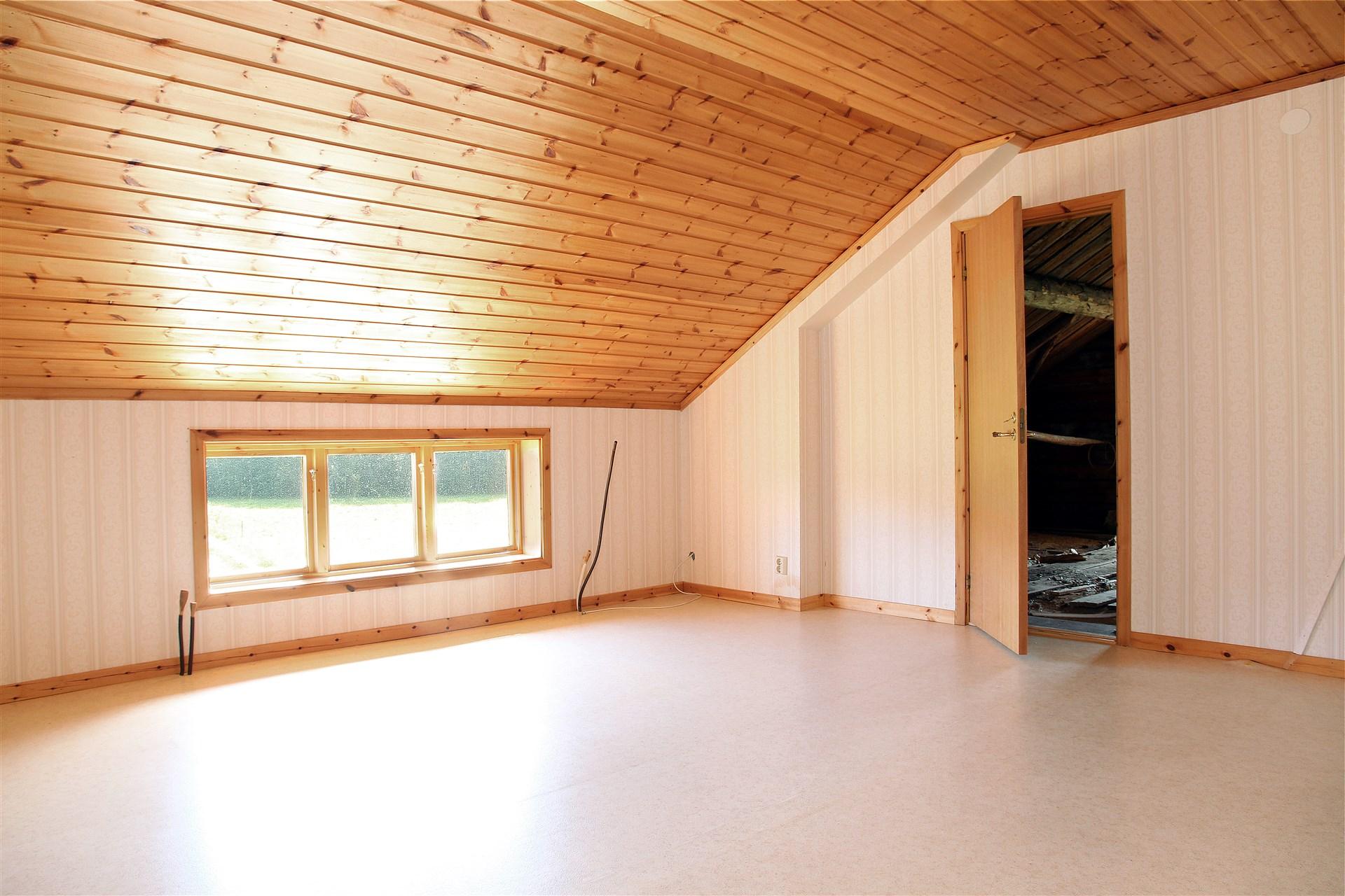 Sovrum med dörr till oinrett rum