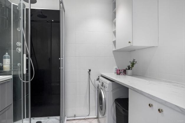 Helkaklat badrum med praktisk arbetsbänk samt bra förvaring.