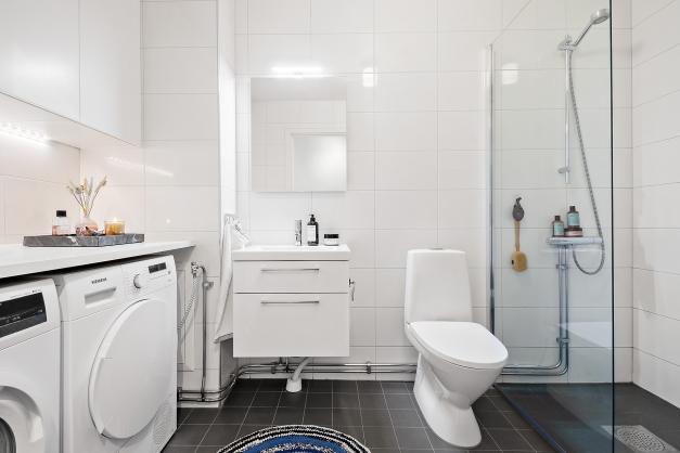 Modernt och fräscht badrum med ljusa väggar och mörkt golv