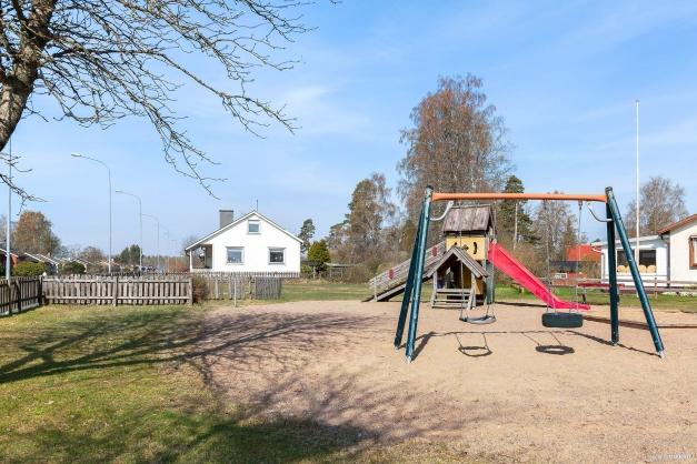 På stenkasts avstånd erbjuder kommunen lekplats för barnen med gungor och rutschkana.