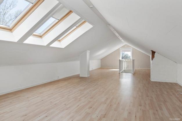 Allrum på övre plan i öppen planlösning med tak- och gavelfönster för ljus och rymd