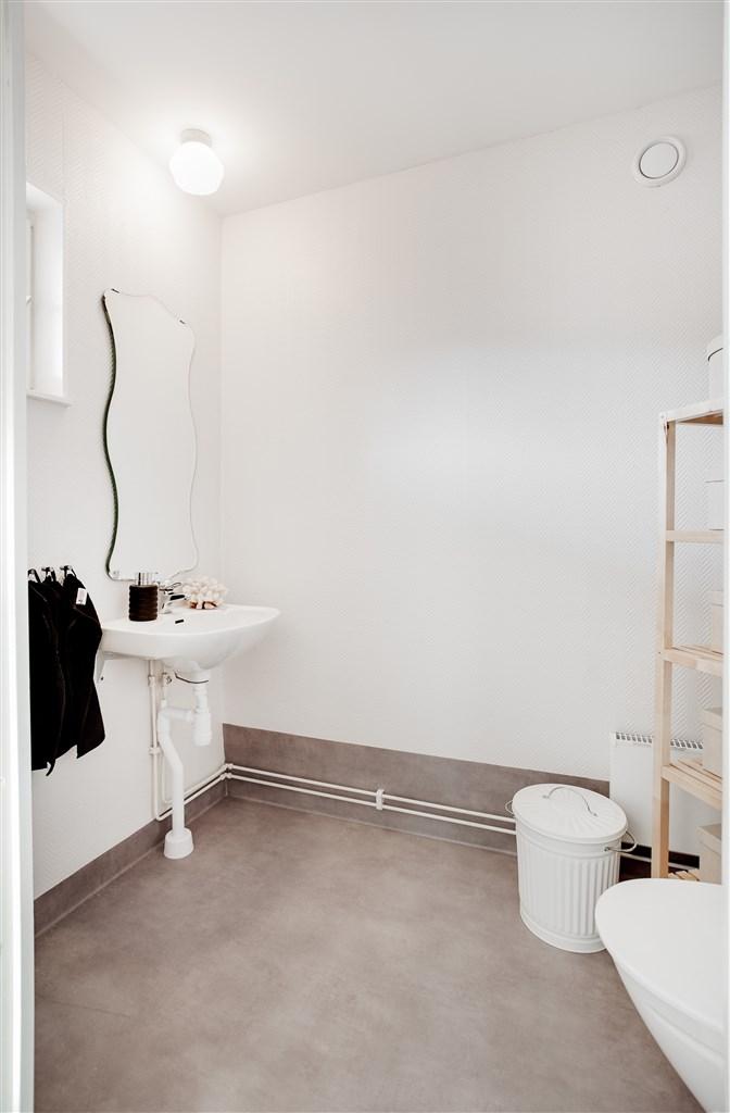 Wc med wc-stol och handfat med fräscha ytskikt.