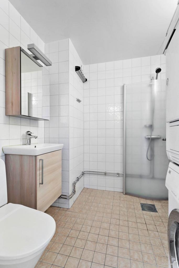 Helkaklat badrum med tvättpelare.
