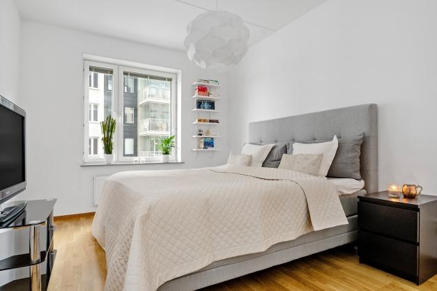 Sovrum med gott om plats för en 180 säng och fönster mot innergården