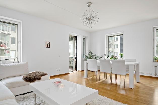 Vardagsrummet med utgång till balkong samt plats för matbord