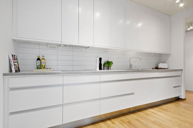 Köket är ljust med vita fronter och vita kakelplattor som stänkskydd