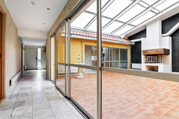 Atrium med öppen spis och skjutbara glaspartier mot övriga huset