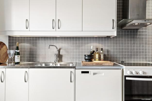 Vitt kök med kakel och klinkergolv i en grå trivsam nyans