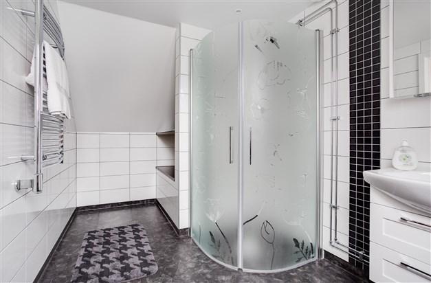 Dusch/wc som är smakfullt inrett med frostade duschdörrar.