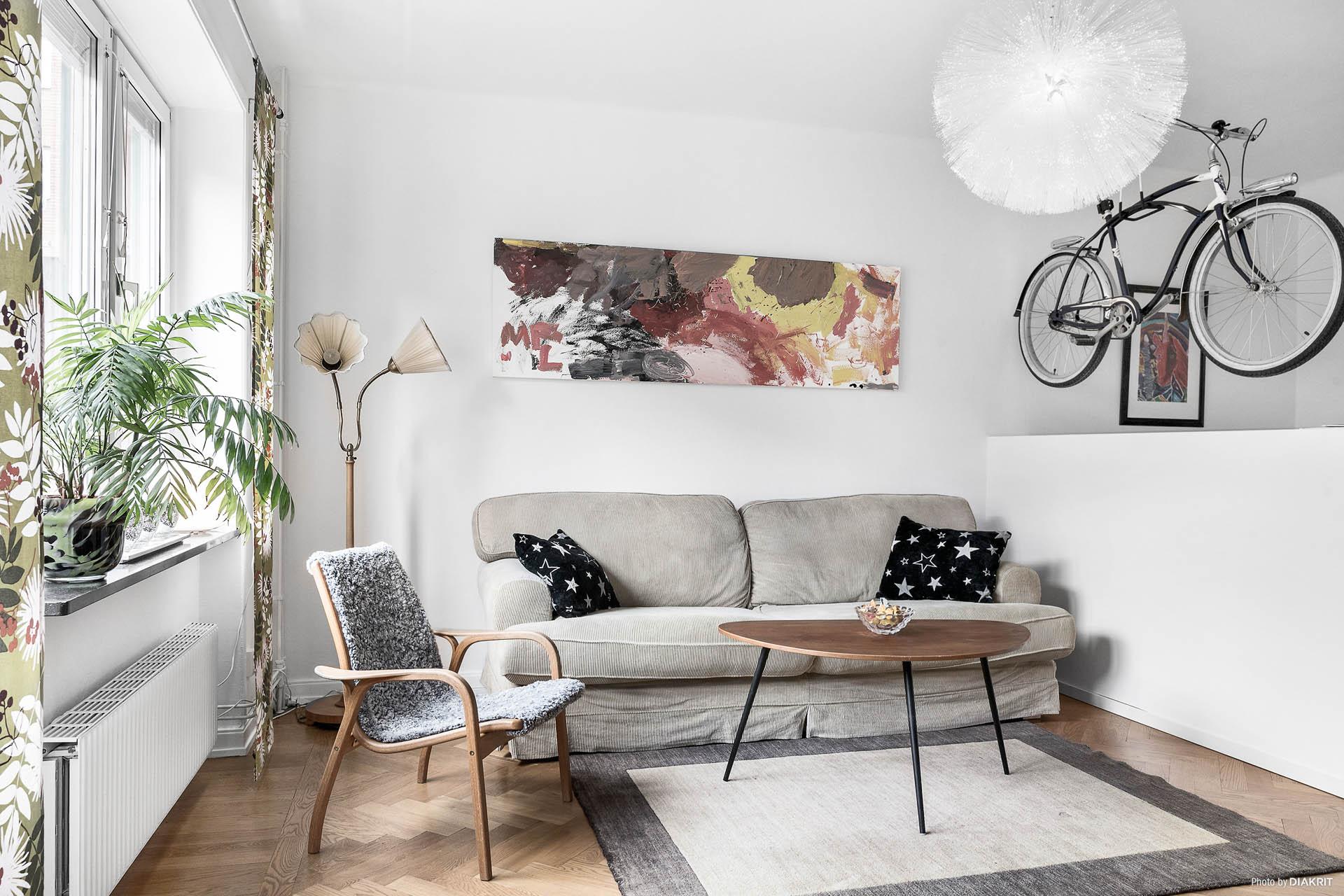 Ljust vardagsrum avdelat med sovplats