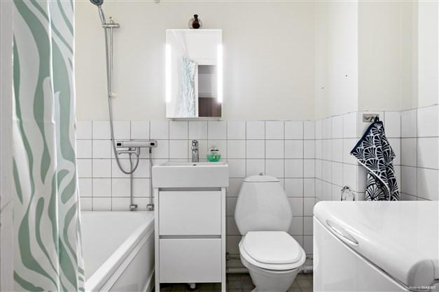 Badrum med badkar och toppmatad tvättmaskin.