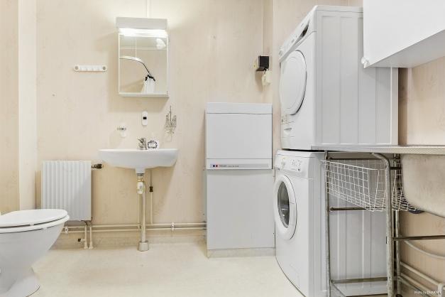 Duschrum med tvättmaskin, torktumlare och tvättho.