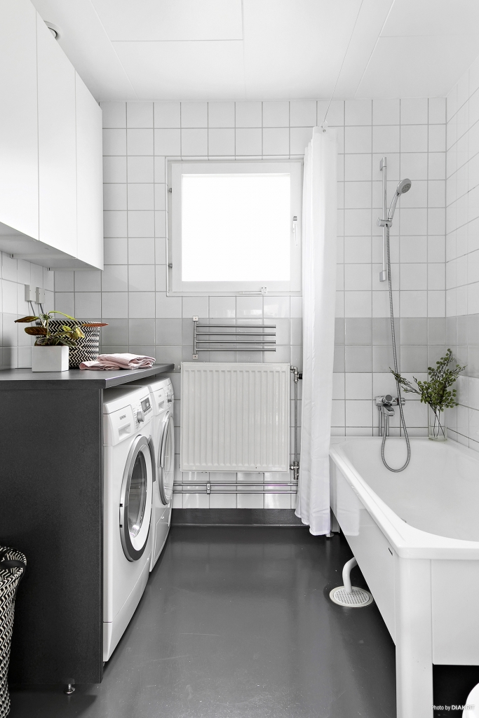 Fräscht badrum med tvättmaskin och torktumlare