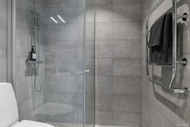 Grå klinkerplattor, rymlig duschhörna och handdukstork