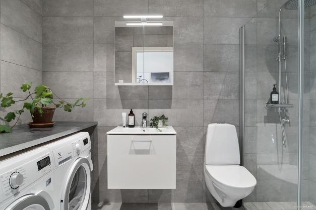 Stort helkaklat badrum med tvättmaskin och torktumlare