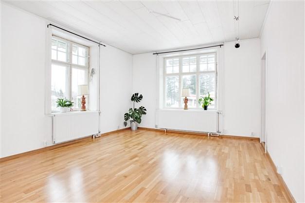 Stort vardagsrum med fina fönsterpartier.