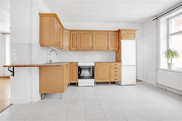 Stort ljust kök med inredning i ek. Klinker på golv med golvvärme.