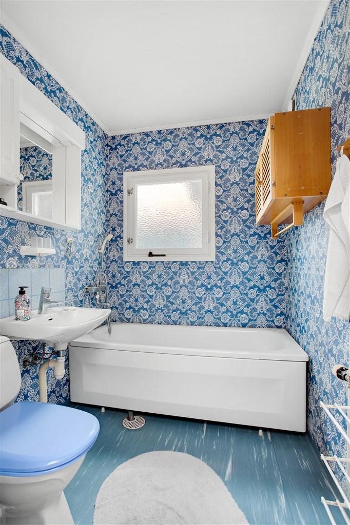Badrum med plastmatta och våtrumstapet. Badrummet är utrustat med vitt porslin.