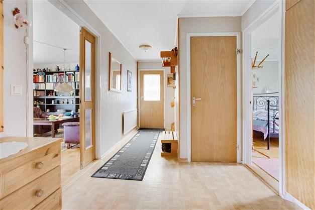 Rymlig hall med trappa till övervåningen och nedgång till källaren.