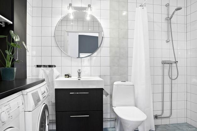 Helkaklat badrum med tvättmöjligheter.
