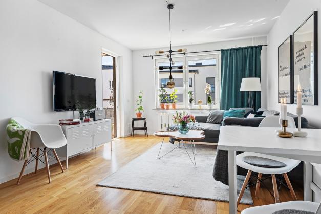 Socialt vardagsrum med öppen planlösning mot köket. Plats för soffa och matbord.