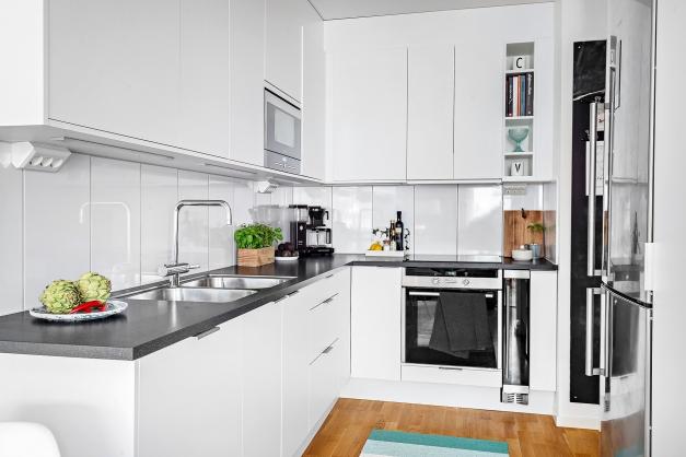 Full utrustat kök med vita köksluckor och vitt kakel stänkskydd.