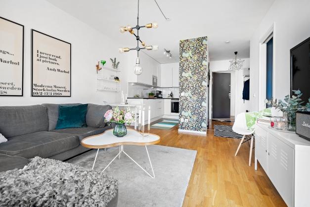 Vardagsrum med genomgående ekparkett golv och vitmålade väggar.