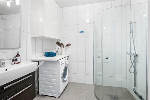 Helkaklat badrum med kombinerad tvättmaskin/torktumlare.