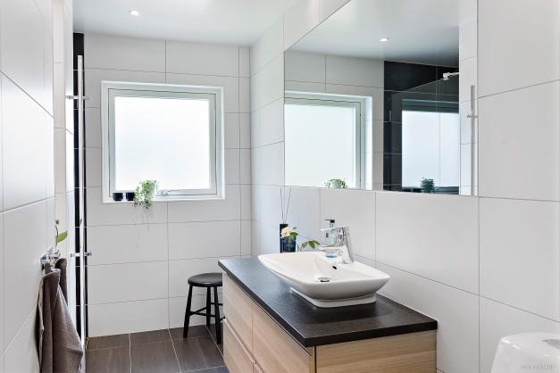BADRUM - Helkaklat stilfullt badrum med öppningsbart fönster och inkaklad stor spegel