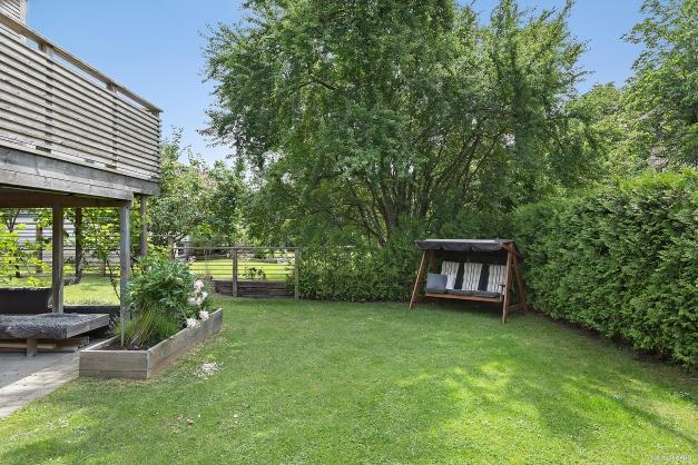 FRAMSIDA - Uppvuxen och inhägnad trädgård med plan gräsmatta