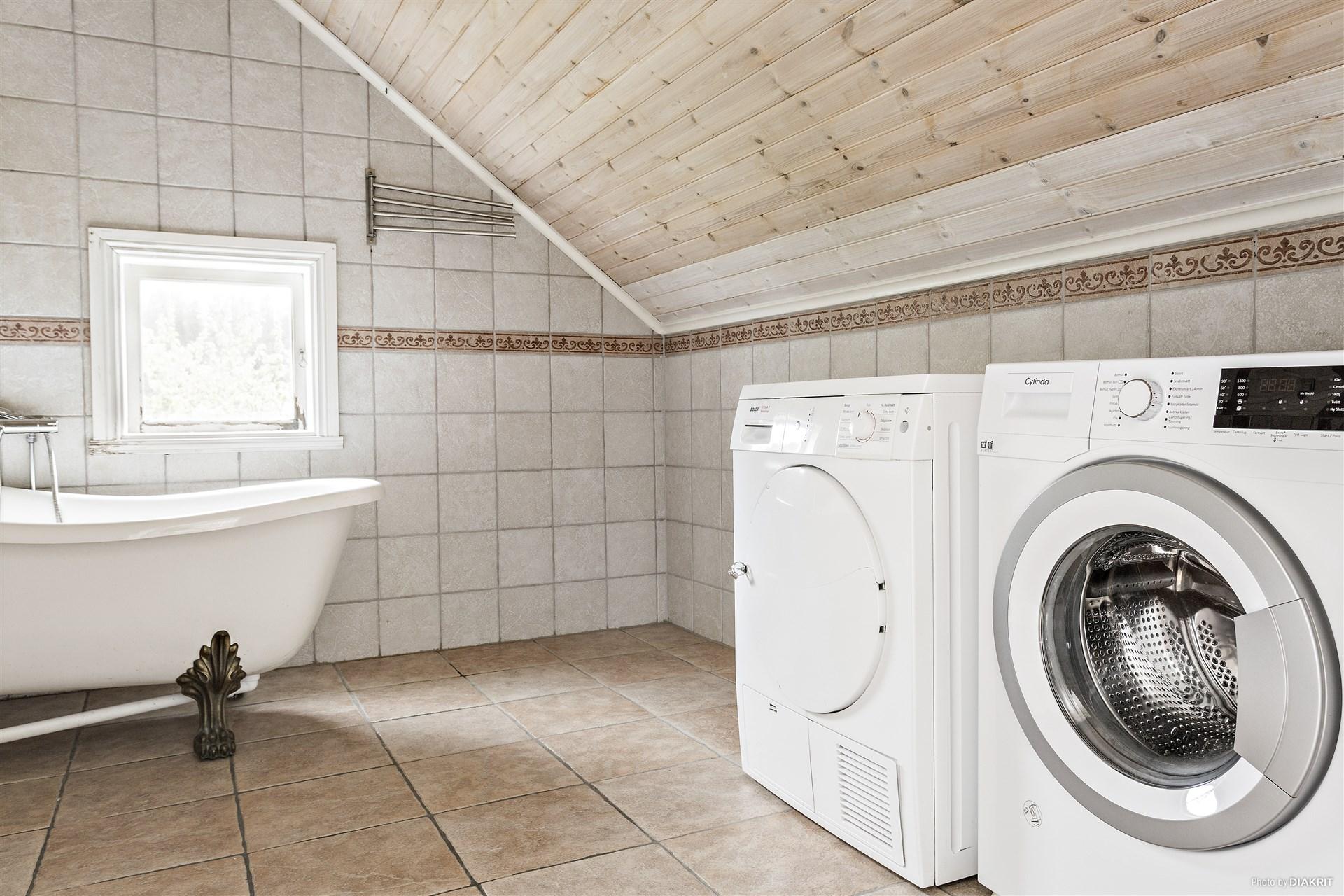 Badrum med klinker och kakel, tvättmaskin, torktumlare och badkar.
