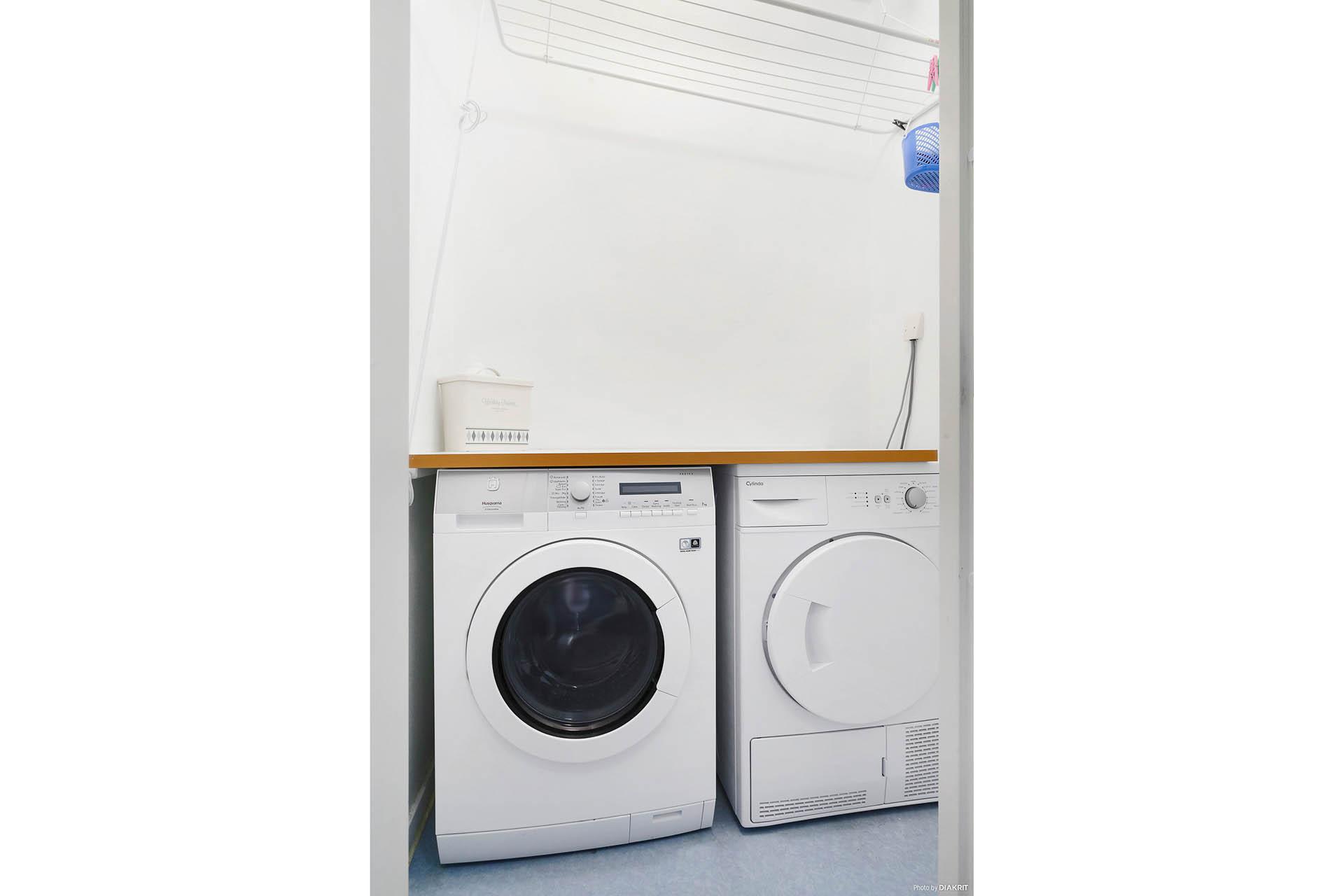 Tvättrum intill hallen med maskiner och torkutrymme.