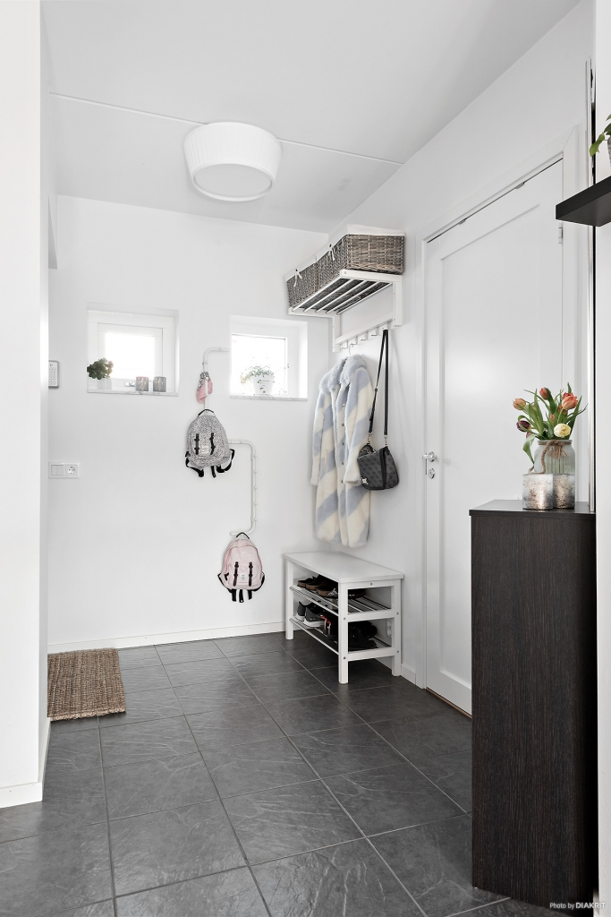 hallen är välkomnande och ljus med plats för kläder och skor, intilliggande tvättstuga har mer plats om man önskar det.