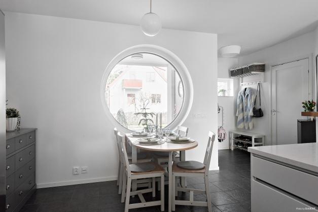 Matplatsen i köket invid fönstret, tåligt klinkergolv i grå ton matchar köket fint