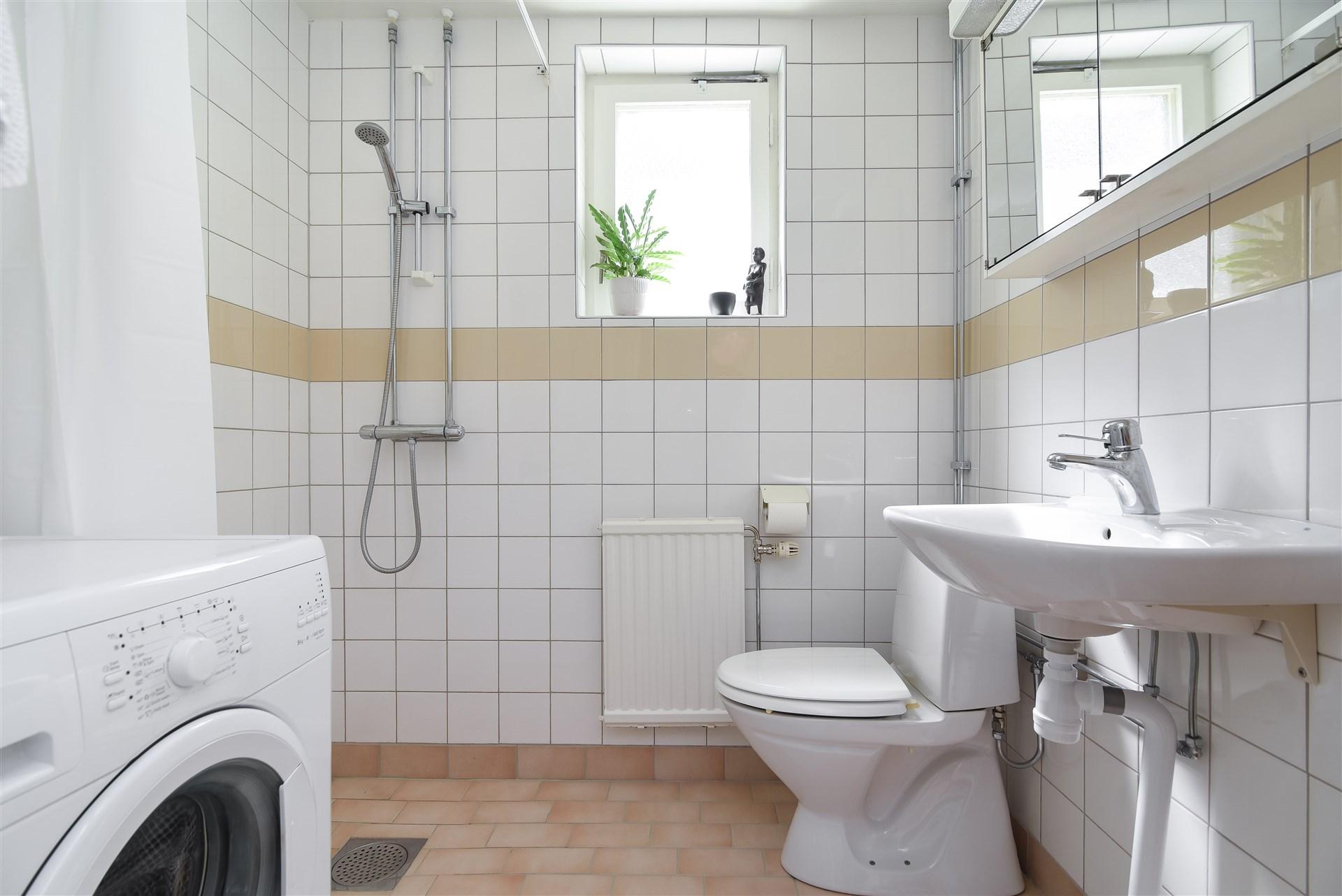 Helkaklat duschutrymme med tvättmaskin.