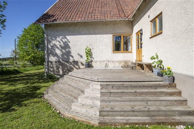 Stor altan i husets vinkel med trappa ner till trädgården