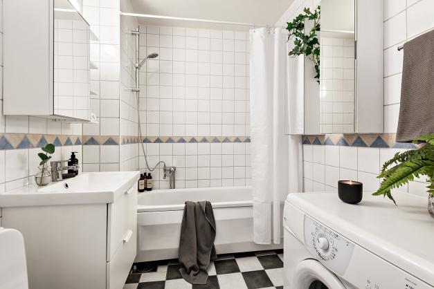 Fräscht badrum med badkar och tvättmaskin