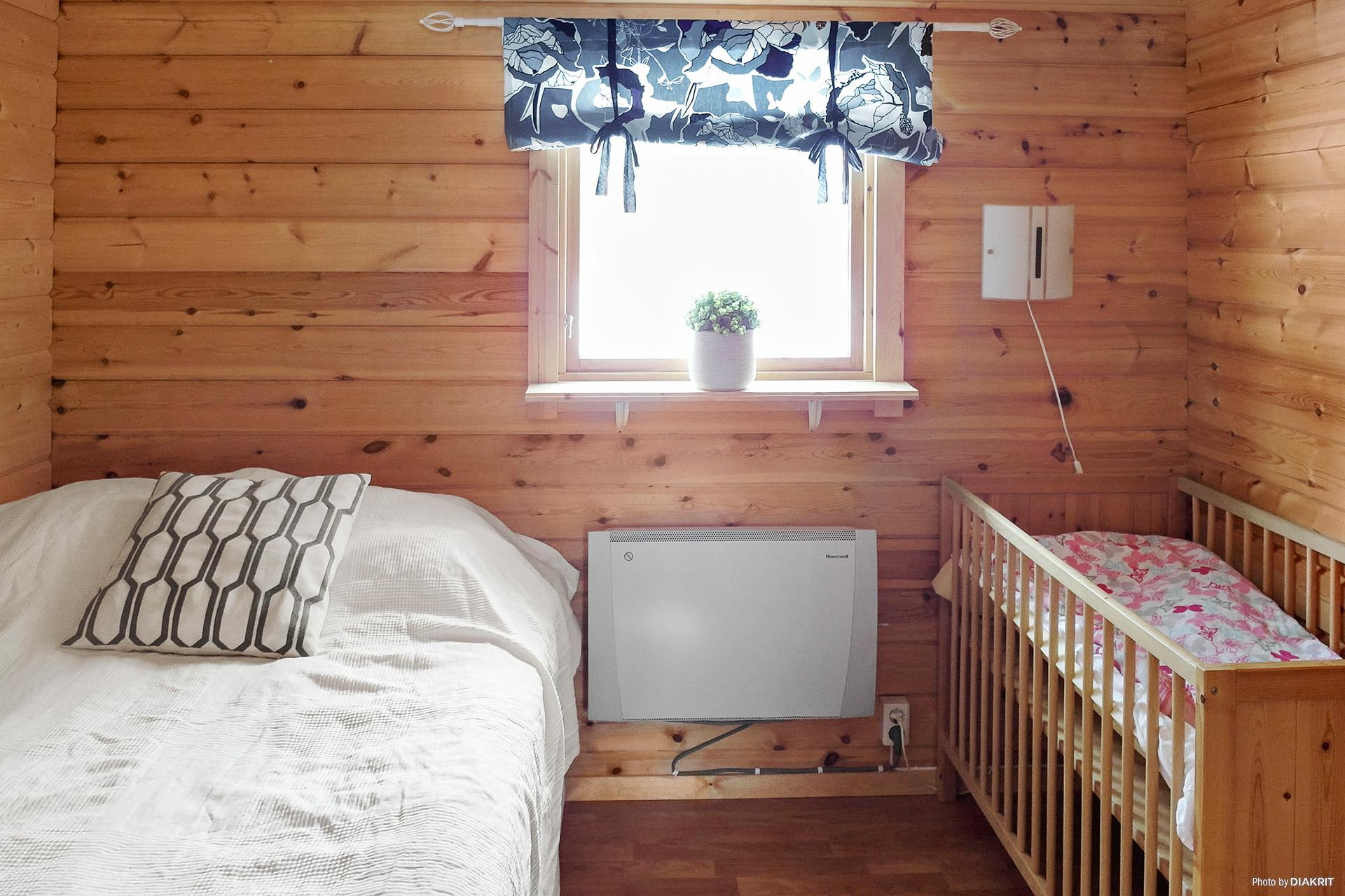 Sovrum med laminatgolv, panelväggar och paneltak.