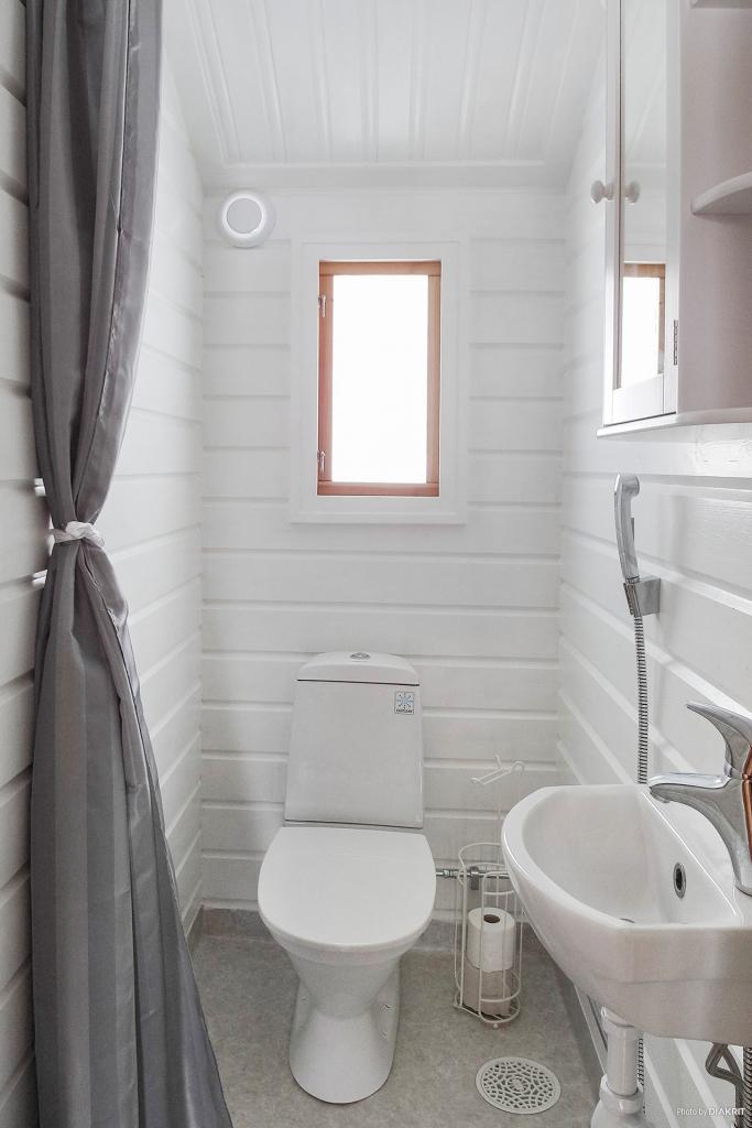 Toalett med wc, tvättställ, handdusch, panelväggar och våtrumsmatta.