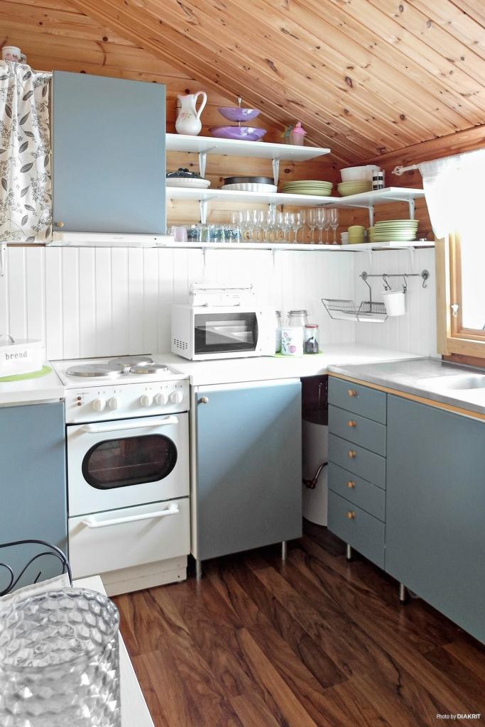 Köksdel med spis m plattor, kyl/frys, målade luckor och laminatgolv.