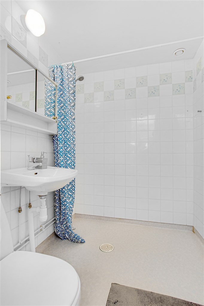 Dusch/wc med plastmatta på golv och kakel på vägg.
